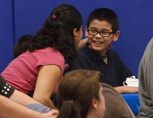 Leah Hogsten  |  The Salt Lake Tribune Edison Elementary fifth-grader Oscar Quintanar receives a hug and a kiss from his mother, Angelina Quintanar, after Oscar was given a netbook computer from Comcast for most improved language arts score in his class. Edison Elementary students learned Thursday about the benefits of connecting to the Internet with hands-on Internet training, an introduction to accessing and reading e-books online and how the use of multi-faceted document cameras donated to the school by Comcast will help improve the education experience for students and teachers.