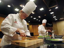 In this Friday, Aug. 24, 2012 photo, Campbell Soup Company chefs Amanda Zimlich, left, and Thomas W. Griffiths prepare fresh produce to add to Campbell's new Green Thai Curry Skillet sauce at the company's headquarters in Camden, N.J. (AP Photo/Mel Evans)