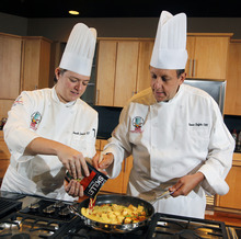 In this Friday, Aug. 24, 2012 photo, Campbell Soup Company chef Thomas W. Griffiths, right, browns fresh produce and tofu as chef Amanda Zimlich pours on Campbell's new Green Thai Curry Skillet sauce at the company's headquarters in Camden, N.J. Last year the company began a quest that led executives to trendsetting cities including Portland, Ore. and London to figure out how to make soups that appeal to younger, finicky customers. In the year ahead, the 143-year-old company plans to roll out 50 new products such as Moroccan Style Chicken and Spicy Chorizo. The ingredients may also surprise those used to a plain bowl of chicken with stars: tomatillos, coconut milk and shitake mushrooms. (AP Photo/Mel Evans)