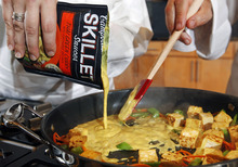 In this Friday, Aug. 24, 2012 photo, Campbell's new Green Thai Curry Skillet sauce is poured over fresh produce and tofu at the Campbell Soup Company headquarters in Camden, N.J. Last year the company began a quest that led executives to trendsetting cities including Portland, Ore. and London to figure out how to make soups that appeal to younger, finicky customers. In the year ahead, the 143-year-old company plans to roll out 50 new products such as Moroccan Style Chicken and Spicy Chorizo. (AP Photo/Mel Evans)