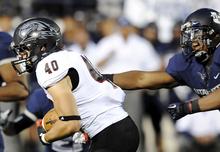 Southern Utah running back Brian Wilson (40) carries the ball as Utah State linebacker Tavaris McMillian defends during their NCAA college football game, Thursday, Aug. 30, 2012, in Logan, Utah. (AP Photo/The Herald Journal, Eli Lucero)