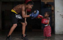 Two-year-old Andrew Theran punches the glove of a young boxer at the Promises From My Neighborhood boxing school in the San Roque neighborhood of Barranquilla, Colombia, Wednesday, Sept. 5, 2012. Amateur boxer Alex Theran, who was born in Barranquilla, sponsors the gym where boys wanting to become boxers are trained free of charge. Andrew is Theran's grandson. (AP Photo/Fernando Vergara)