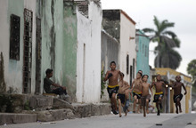 Boys from the Promises From My Neighborhood boxing school run through the streets, some barefoot, of the San Roque neighborhood in Barranquilla, Colombia, Wednesday, Sept. 5, 2012. Amateur boxer Alex Theran, who was born in Barranquilla, sponsors the gym where boys wanting to become boxers are trained free of charge. (AP Photo/Fernando Vergara)