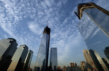 One World Trade Center, center, rises above the National September 11 Memorial and Museum at the World Trade Center, Thursday, Sept. 6, 2012 in New York. Tuesday will mark the eleventh anniversary of the terrorist attacks of Sept. 11, 2001. The World Financial Center is on the left, and Four World Trade Center is at right. (AP Photo/Mark Lennihan)