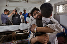An unidentified man comforts a wailing relative of Ghulam Hassan Rather after identifying his body in Srinagar, India, Friday, Sept. 7, 2012. Two people died while 17 others were injured when a passenger bus skidded off the road in central Kashmir's Budgam district, according to a local news agency. (AP Photo/Dar Yasin)