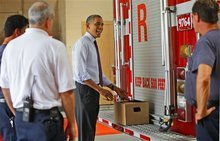 President Barack Obama, center, opens up a box containing bottles of White House brewed beer that he was delivering to the firefighters at Fire Station No. 14, during an unscheduled stop, Tuesday, Sept. 4, 2012, in Norfolk, Va. (AP Photo/Pablo Martinez Monsivais)