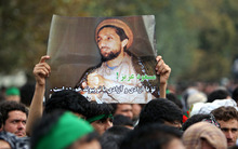 An Afghan man holds a portrait of Ahmad Shah Massoud during a ceremony commemorating the11th anniversary of his death in Kabul, Afghanistan, Saturday, Sept, 8, 2012. The charismatic Northern Alliance commander was killed in an al-Qaida suicide bombing two days before the Sept. 11, 2001 attacks. Urdu on poster reads,