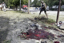 A French soldier from NATO forces walks past the scene of a suicide attack in Kabul, Afghanistan, Saturday, Sept. 8, 2012. A suicide bomber blew himself up near NATO headquarters in the Afghan capital on Saturday, killing at least six people, police said. (AP Photo/Musadeq Sadeq)