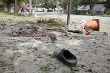 Shoes and blood remain at the scene of a suicide attack in Kabul, Afghanistan, Saturday, Sept. 8, 2012. A suicide bomber blew himself up near NATO headquarters in the Afghan capital on Saturday, killing at least six people, police said. (AP Photo/Musadeq Sadeq)