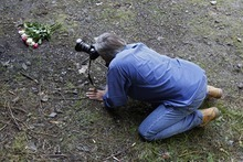 A photographer takes pictures of flowers on the crime scene where four people have been shot to death in a British-registered car, in a forest in the Alps, near Chevaline, French Alps, Saturday, Sept. 8, 2012. The case took on international ramifications, with links that tied the slain family to Britain, Iraq and Sweden. (AP Photo/Laurent Cipriani)