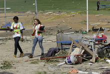 American Red Cross workers walk past a pile of debris as they come to the assistance of cabana owners at the Breezy Point Surf Club after a possible tornado touched down in the area in the Queens section of New York, Saturday, Sept. 8, 2012.  A tornado swept out of the sea and hit the beachfront neighborhood in New York City, hurling debris in the air, knocking out power and startling residents who once thought of twisters as a Midwestern phenomenon. Firefighters were still assessing the damage, but no serious injuries were reported and the area affected by the storm appeared small. (AP Photo/Kathy Willens)