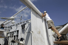 Cabana owner Bill Ryan looks into other roofless cabanas at the Breezy Point Surf Club in New York, Saturday, Sept. 8, 2012, after a severe weather storm passed the area. A tornado swept out of the sea and hit the beachfront neighborhood in New York City, hurling debris in the air, knocking out power and startling residents who once thought of twisters as a Midwestern phenomenon. Firefighters were still assessing the damage, but no serious injuries were reported and the area affected by the storm appeared small. (AP Photo/Kathy Willens)