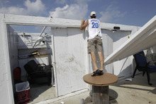 Cabana owner Bill Ryan looks into other roofless cabanas at the Breezy Point Surf Club in New York, Saturday, Sept. 8, 2012, after a possible tornado touched down in the area during severe weather.  Ryan's cabana also lost it's roof in the storm.  A tornado swept out of the sea and hit the beachfront neighborhood in New York City, hurling debris in the air, knocking out power and startling residents who once thought of twisters as a Midwestern phenomenon. Firefighters were still assessing the damage, but no serious injuries were reported and the area affected by the storm appeared small.(AP Photo/Kathy Willens)