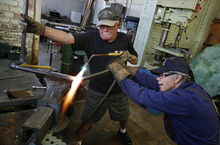 Scott Sommerdorf  |  The Salt Lake Tribune              Richard Carroll, left, and Bob Wachs work on bending a shaft of steel to make a decoupler arm for the locomotive they are working to restore. A group of volunteers in Ogden comes together every Saturday to work on restoring a narrow gauge locomotive at the Union Station Trainmen's Building, Saturday, September 8, 2012.