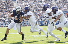 Chris Detrick  |  The Salt Lake Tribune Brigham Young Cougars quarterback Taysom Hill (4) scores a touchdown while being face-masked by Weber State Wildcats linebacker Anthony Morales (44) during the first half of the game against Weber State at LaVell Edwards Stadium Saturday September 8, 2012. BYU is winning the game 21-0.