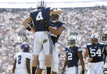 Chris Detrick  |  The Salt Lake Tribune Brigham Young Cougars quarterback Taysom Hill (4) and Brigham Young Cougars tight end Kaneakua Friel (82) celebrate after Hill scored a touchdown during the first half of the game against Weber State at LaVell Edwards Stadium Saturday September 8, 2012. BYU is winning the game 21-0.