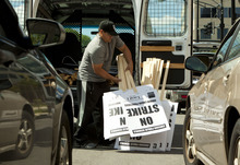 A man delivers signs saying