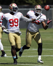 FILE - In this Aug. 7, 2012, file photo, San Francisco 49ers linebackers Aldon Smith (99) and Ahmad Brooks (55) reach for the ball during NFL football practice in Santa Clara, Calif. They are not only the biggest reason behind the 49ers' defensive success, they are a close bunch that has quickly become the new NFL standard for linebackers. Meet Patrick Willis, NaVorro Bowman, Aldon Smith and Ahmad Brooks. (AP Photo/Jeff Chiu, File)