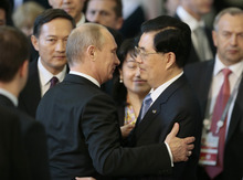 Russian President Vladimir Putin, left, embraces Chinese President Hu Jintao following the leaders group photo on the final day of the APEC summit in Vladivostok, Russia, Sunday, Sept. 9, 2012. (AP Photo/Mikhail Metzel)