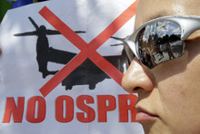 Demonstrators take part in a rally around the National Diet building against the United States' plans to deploy Osprey aircraft on a southern Japanese island amid renewed safety concerns, in Tokyo, Sunday, Sept. 9, 2012.  (AP Photo/Shizuo Kambayashi)