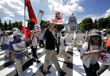 Demonstrators stage a rally around the National Diet building against the United States' plans to deploy Osprey aircraft on a southern Japanese island amid renewed safety concerns, in Tokyo, Sunday, Sept. 9, 2012. (AP Photo/Shizuo Kambayashi)