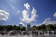 Demonstrators gather to form a human chain during a rally around the National Diet building against the United States' plans to deploy Osprey aircraft on a southern Japanese island amid renewed safety concerns, in Tokyo, Sunday, Sept. 9, 2012. (AP Photo/Shizuo Kambayashi)