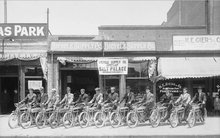 Image shows a row of men sitting on their motorcycles July 29, 1911 on the sidewalk  in front of the Bicycle Supply Company at 64 West and 300 South in Salt Lake. Courtesy of Utah Historical Society