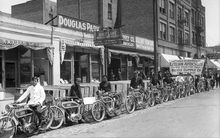 Image shows a row of men standing with a new shipment of motorcycles May 21, 1913 in front of the Bicycle Supply Company at 64 West 300 South in Salt Lake. Courtesy of Utah Historical Society