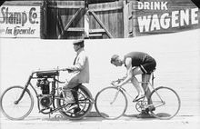 Image shows a cyclist chasing a motor-powered bicycle at the Salt Palace, July 16, 1906. Courtesy of Utah Historical Society
