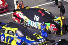 Cars for Kyle Busch (18) and Matt Kenseth (17) are covered during a rain delay at the NASCAR Sprint Cup Series auto race at Richmond International Raceway in Richmond, Va., Saturday, Sept. 8, 2012. (AP Photo/Jason Hirschfeld)