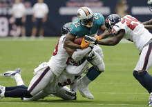 Miami Dolphins running back Reggie Bush (22) pulls three Houston Texans defenders, Johnathan Joseph (24), Danieal Manning (38) and Glover Quin, left, for a first down in the first quarter of an NFL football game on Sunday, Sept. 9, 2012, in Houston. (AP Photo/David J. Phillip)