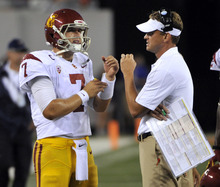Southern California coach Lane Kiffin, right, talks with quarterback Matt Barkley during the fourth quarter of an NCAA college football game against Syracuse on Saturday, Sept. 8, 2012, in East Rutherford, N.J. USC defeated Syracuse 42-29. (AP Photo/Bill Kostroun)
