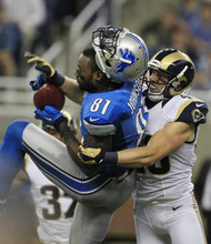 St. Louis Rams strong safety Craig Dahl (43) knocks off the helmet of Detroit Lions wide receiver Calvin Johnson (81) after Johnson's 51-yard reception during the second quarter of an NFL football game in Detroit, Sunday, Sept. 9, 2012. (AP Photo/Carlos Osorio)