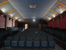 In this photo from Sept. 4, 2012, a lone spectator enters the Isis movie theatre for the 6:30 showing of a movie, in Crete, Neb. The Isis Theatre hasn't changed much since it opened 86 years ago, but as the movie industry phases out the traditional 35 mm film reels in favor of digital media, the Isis' owner must come up with $85,000 to buy new projection equipment, computers, a sound system and even a different screen. It is a huge financial burden for the small theatre. (AP Photo/Nati Harnik)