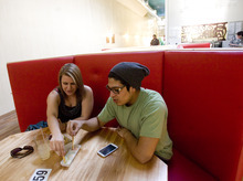 Kim Raff | The Salt Lake Tribune (left) Emily Nichols and Stefan Sanchez share a plate of fries in a booth at CO2 Cafe, a newly opened cafe in a renovated building on Main Street in Salt Lake City, Utah on September 8, 2012. Mike Wirthlin, who owns the cafe with his wife Niki Nichols, is a former analyst for the CIA who came to Salt Lake City to open a gathering place for the community.