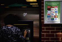 In this July 16, 2012 photo, credit logos are seen as a consumer withdrawals money from an ATM in Atlanta. Americans cut back on borrowing in July for the first time in nearly a year. Credit card use fell for the second straight month, suggesting many consumers remain cautious in the face of high unemployment and slow growth. (AP Photo/David Goldman)