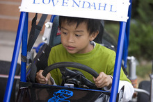 Paul Fraughton | Salt Lake Tribune Isaiah Heng, a first grader at Silver Hills Elementary School in Kearns, sits behind the wheel of  The pair joined students and families at for a PTA event  where race drivers from Rocky Mountain Raceway  brought their  race cars to the school so kids could get an up close experience with the unique machines.  Monday, September 10, 2012