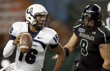 Utah State quarterback Chuckie Keeton (16)  in the Hawaii defensive tackle Zach Masch (9) in the first quarter of an NCAA college football game, Saturday, Nov. 5, 2011, in Honolulu. (AP Photo/Eugene Tanner)
