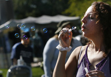 Scott Sommerdorf  |  The Salt Lake Tribune              Michelle Quintana blows bubbles to try to generate interest in the Crone's Hollow booth at the Annual Pagan Pride Day at Murray Park, Sunday, September 9, 2012.