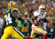 San Francisco 49ers' Vernon Davis (85) tries to break away from Green Bay Packers' Jarrett Bush (24) during the second half of an NFL football game Monday, Sept. 10, 2012, in Green Bay, Wis. The 49ers won 30-22. (AP Photo/Mike Roemer)
