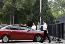 Chinese plain clothes security personnel stop a man from ramming his car against the gate of the Japanese embassy in Beijing, China Tuesday, Sept. 11, 2012. Chinese government ships are patrolling near contested East China Sea islands in a show of anger after Tokyo moved to assert its control in the area. Beijing warned Monday that Japan would suffer unspecified consequences if Tokyo purchased the islands from private owners, as it formally did Tuesday.(AP Photo/Ng Han Guan)