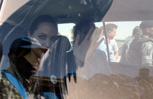 The U.N. refugee agency's special envoy, actress Angelina Jolie, waves through the dusty window of her car as she departs the Zaatari Refugees Camp in Jordan for Syrians who fled the civil war in their country, Tuesday, Sept. 11, 2012. Jolie said Tuesday she heard