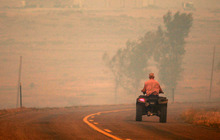 A man rides a four-wheeler along Hat 6 Road through thick smoke from the Casper Mountain wildfire on Monday, Sept. 10, 2012 in Casper, Wyo. The fire spread rapidly eastward Monday morning and had burned about 10,000 acres by 1 p.m. (AP Photo/Star-Tribune, Alan Rogers)
