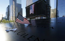 An American flag is inserted in one of the of names engraved at the north reflecting pool at the World Trade Center Memorial, during the 11th anniversary observance of the attacks at the World Trade Center, in New York, Sept. 11 2012. (AP Photo/Mike Segar, Pool)