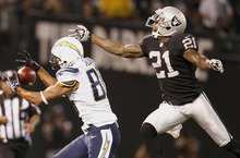 San Diego Chargers wide receiver Malcom Floyd (80) catches a pass in front of Oakland Raiders defensive back Ron Bartell (21) during the first half of an NFL football game in Oakland, Calif., Monday, Sept. 10, 2012. (AP Photo/Tony Avelar)