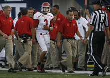 Scott Sommerdorf  |  The Salt Lake Tribune              Utah QB Jordan Wynn heads to the locker room holding his previously injured left shoulder as head coach Kyle Whittingham gets a report from assistants in the background during the game against Utah State on Friday, Sept. 7, 2012.