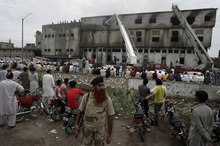 People gather at the site of burnt garment factory in Karachi, Pakistan on Wednesday, Sept. 12, 2012. Pakistani officials say the death  toll from devastating factory fires that broke out in two major cities has risen to 128. Hospital official Tariq Kaleem said the fire at a garment factory in the southern Pakistani city of Karachi killed 103 people. A blaze at a shoe factory in the eastern city of Lahore killed 25 people. (AP Photo/Fareed Khan)