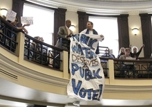 A banner-wielding protester struggles with a security officer in the balcony of City Hall during a City Council vote on whether to add fluoride to city water in Portland, Ore., Wednesday, Sept. 12, 2012. The City Council approved a plan Wednesday to add fluoride to Portland's water, meaning Oregon's biggest city is no longer the largest holdout in the U.S.  The protestor was removed from Council chambers. (AP Photo/Don Ryan)