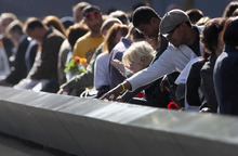 Family members view the names of their relatives etched into the 9/11 Memorial during the commemoration of the eleventh anniversary of the terrorist attacks on the World Trade Center, Tuesday, Sept. 11, 2012 in New York . Begum, who is from Bangladesh, lost her nephew Nural Miah and his wife Shakila Yasmin, who were two of the many Muslims who also died in the attacks. New York City is commemorating the eleventh anniversary of the September 11, 2001 attacks.  (AP Photo/John Moore, Pool)