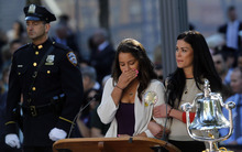 A woman becomes emotional after reading the name of her father as friends and relatives of the victims of 9/11 gather for a ceremony marking the 11th anniversary of the attacks at the National September 11 Memorial at the World Trade Center site, Tuesday, Sept. 11, 2012, in New York. (AP Photo/Jason DeCrow)